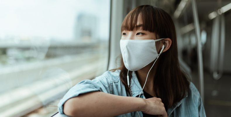 a young woman sitting on a train, wearing a face mask.